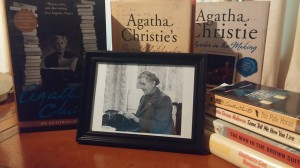 Photograph of Agatha Christie typing, surrounded by books about and by her.