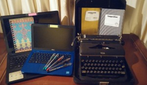 Left to right - Laptop, blank book, netbook, pens, typewriter, composition books.