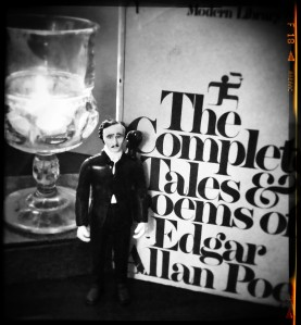 Edgar Allan Poe (writer, adventurer, action figure) standing next to a collection of his work.